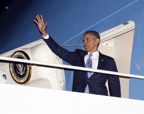 President Barack Obama waves as he boards Air