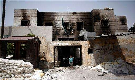 A Syrian boy stands in the rubble of
