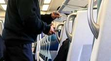 An LIRR conductor punches tickets on an eastbound