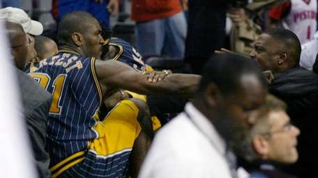 Pacers forward Ron Artest gets into the stands