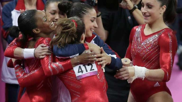 U.S. gymnasts celebrate after their routine on the