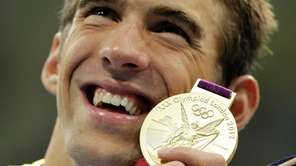 Michael Phelps poses with his gold medal for