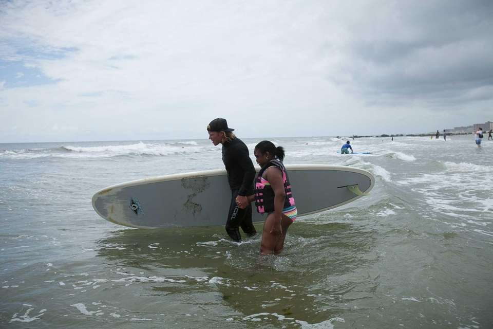 Tamika Thompson, 11, learns to surf with a