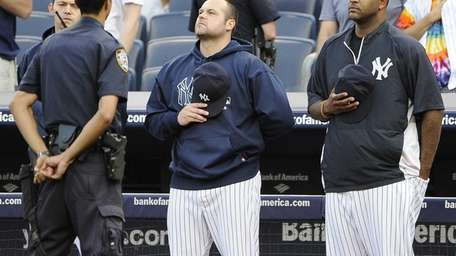 Joba Chamberlain and CC Sabathia stand at attention