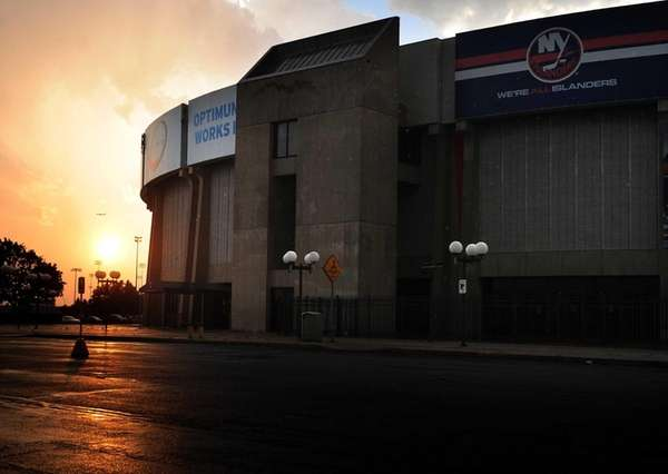 The sun sets behind the Nassau Coliseum in