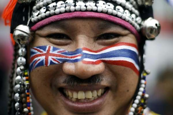A spectator from Thailand wears traditional clothes and