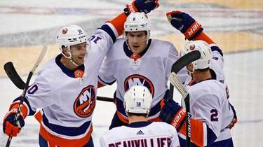 The Islanders' Ryan Pulock (top) celebrates with teammates
