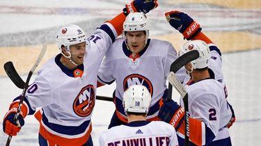 The Islanders' Ryan Pulock (top) celebrates with teammates
