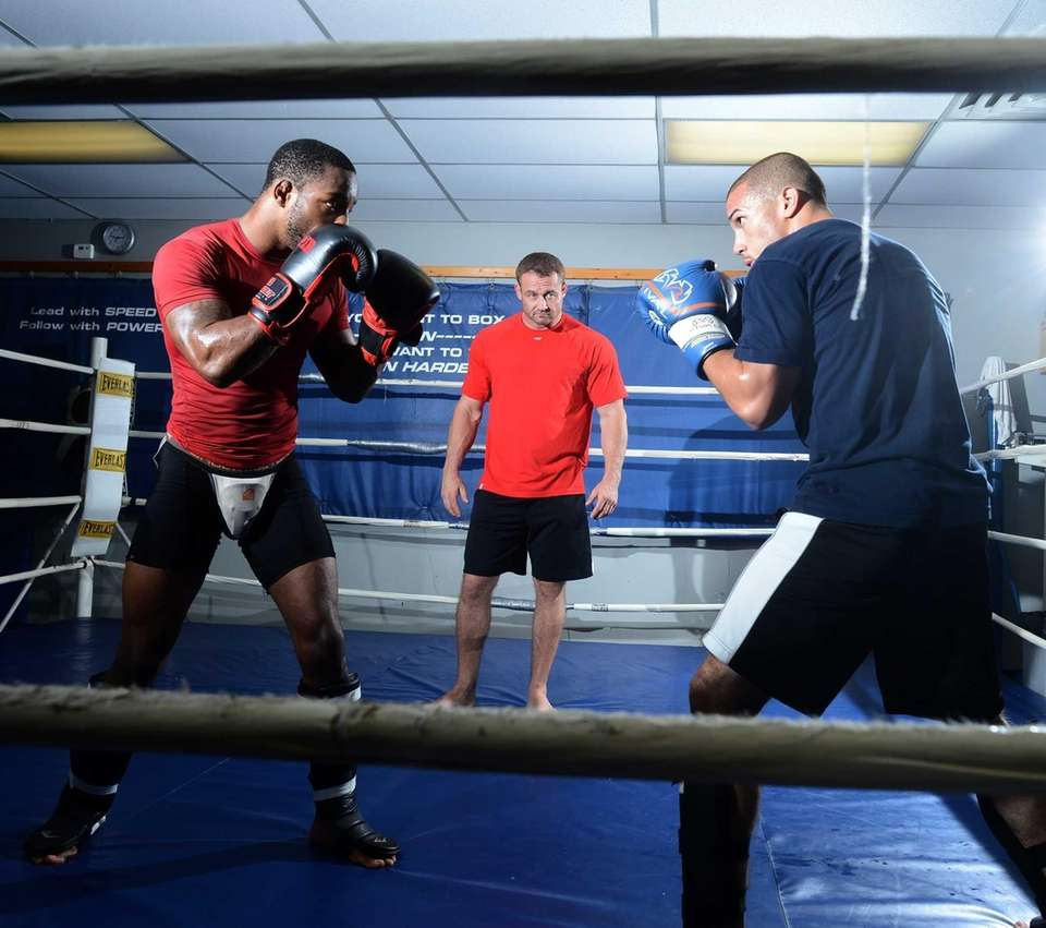 Keith Trimble, center, of Bellmore Kickboxing/MMA watches Andre
