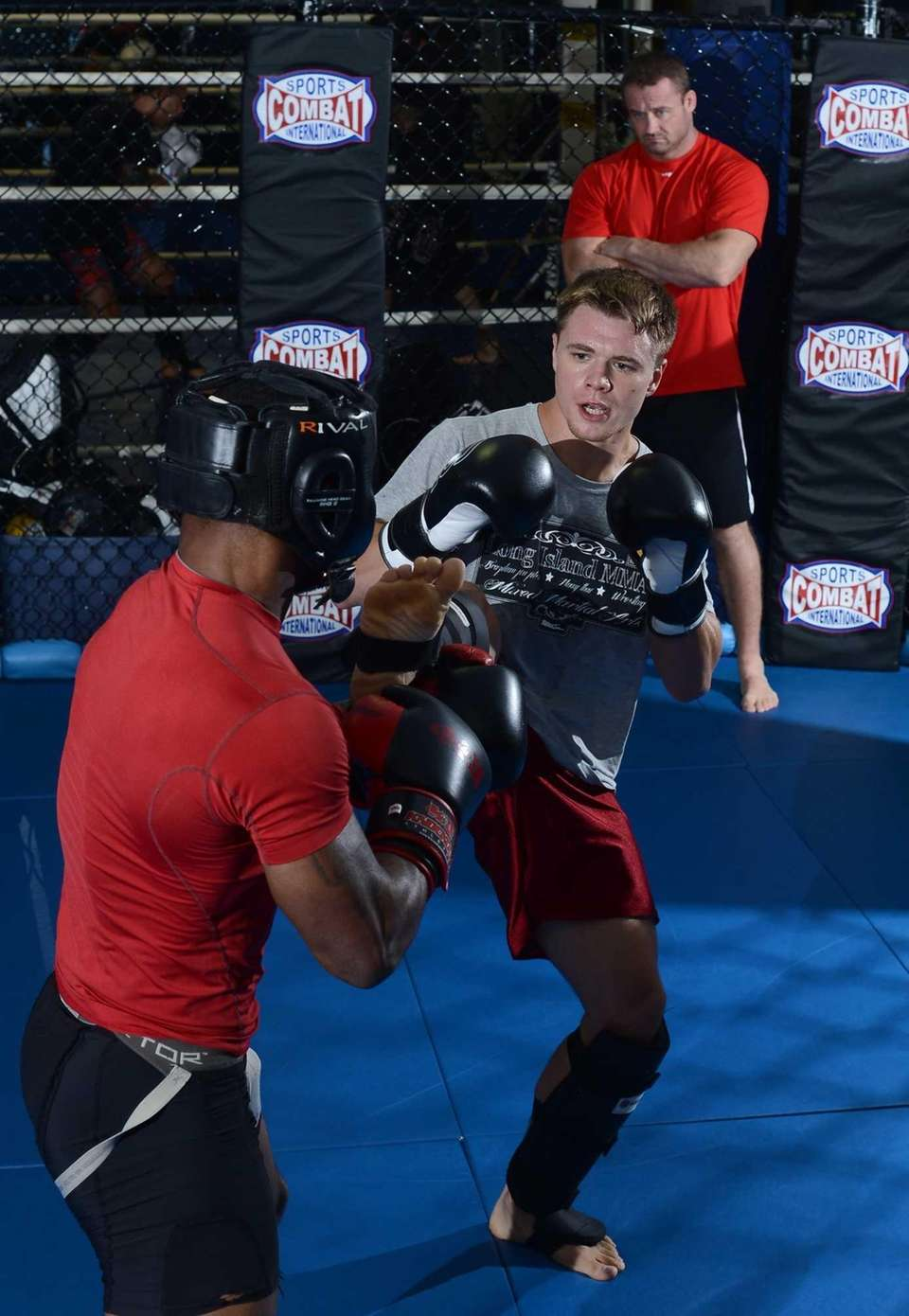 Keith Trimble, center, of Bellmore Kickboxing Academy watches