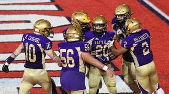 Sayville players celebrate a touchdown by CJ Messina