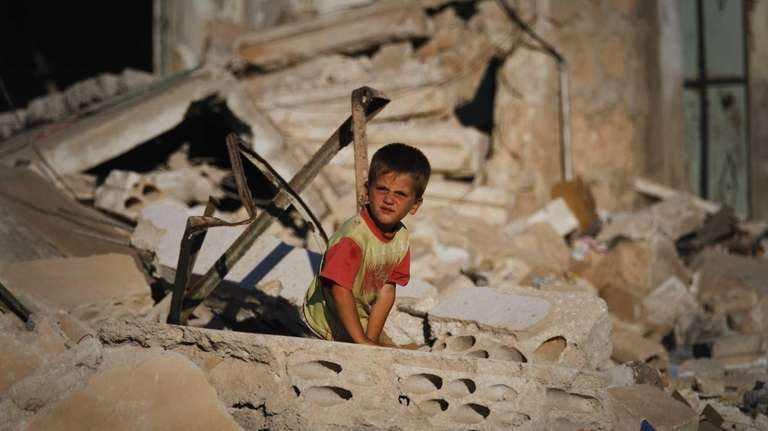 A Syrian boy sits in the rubble of