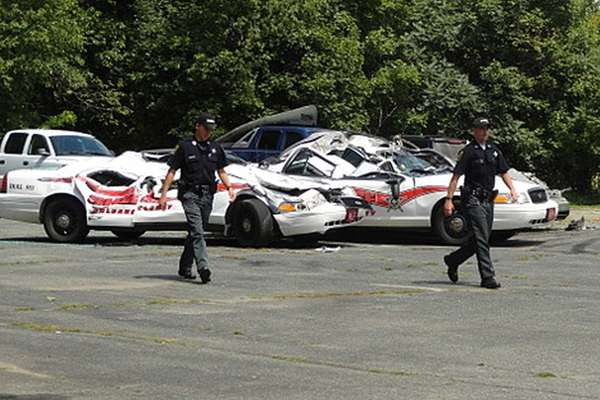 Sheriff officers walk past crushed cruisers at the