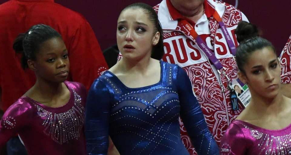 Russian gymnast Aliya Mustafina stands between U.S. gymnasts