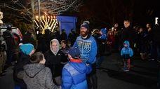 Rabbi Dovid Weinbaum dances with kids at Hanukkah