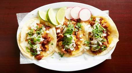 Al pastor tacos are topped with cilantro and