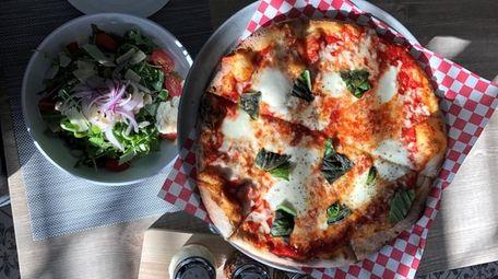 A thin-crust margherita pizza and arugula salad at