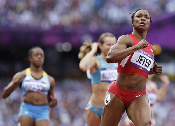 Carmelita Jeter, right, crosses the finish line in