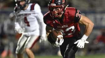 Dion Kuinlan #33 of Plainedge rushes for a