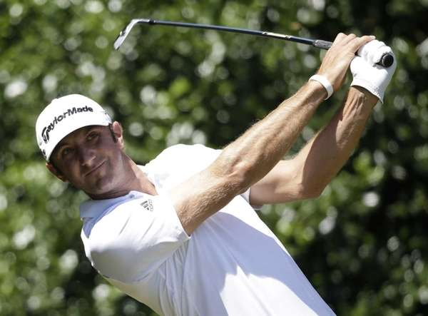 Dustin Johnson plays a shot off the first