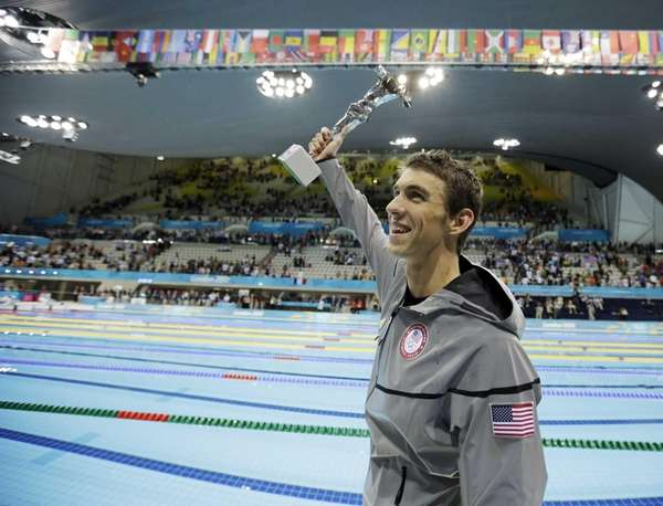 Michael Phelps holds up a trophy after being