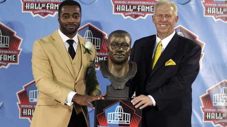 Former NFL player Curtis Martin, left, poses with