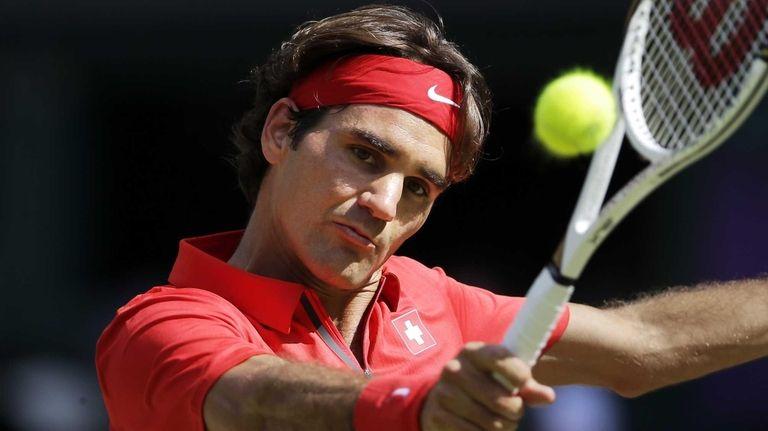 Switzerland's Roger Federer returns a shot to Britain's