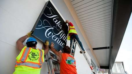 Workers hang the sign for the Saks Fifth