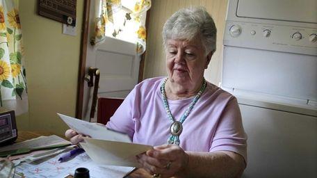 Neta Homier looks over bills in her home