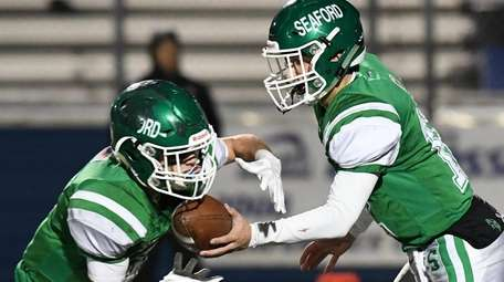 Seaford quarterback Logan Masters hands the ball off