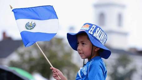 Jose Chavez, 5, of Huntington waves the El