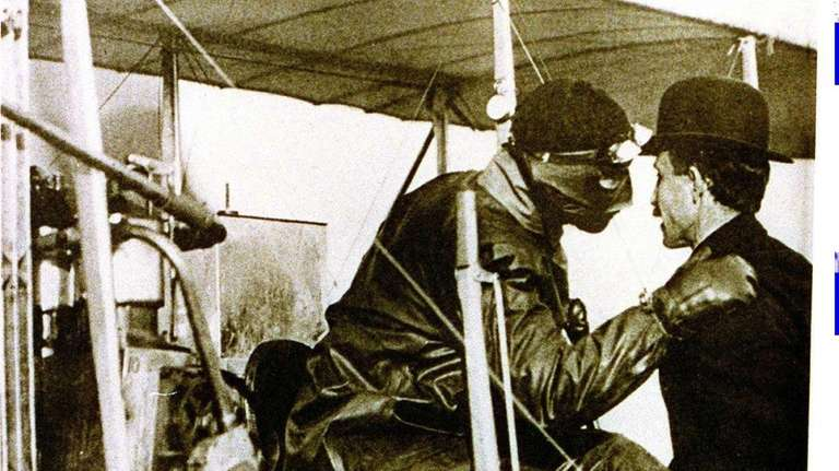 Orville Wright, right, talks to a pilot just