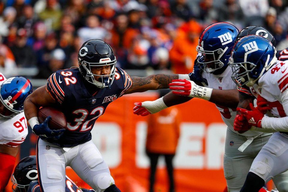 Chicago Bears running back David Montgomery pushes off
