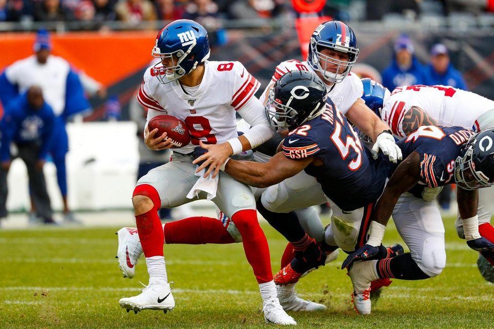 Giants quarterback Daniel Jonesescapes the grasp of Chicago