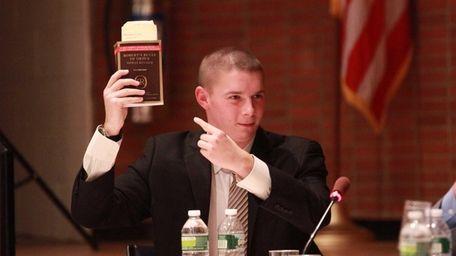 School board member Joshua Lafazan holds up Robert's