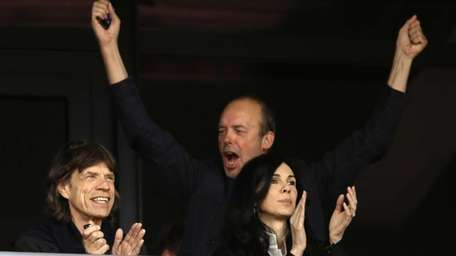 Musician Mick Jagger, left, watches an evening session