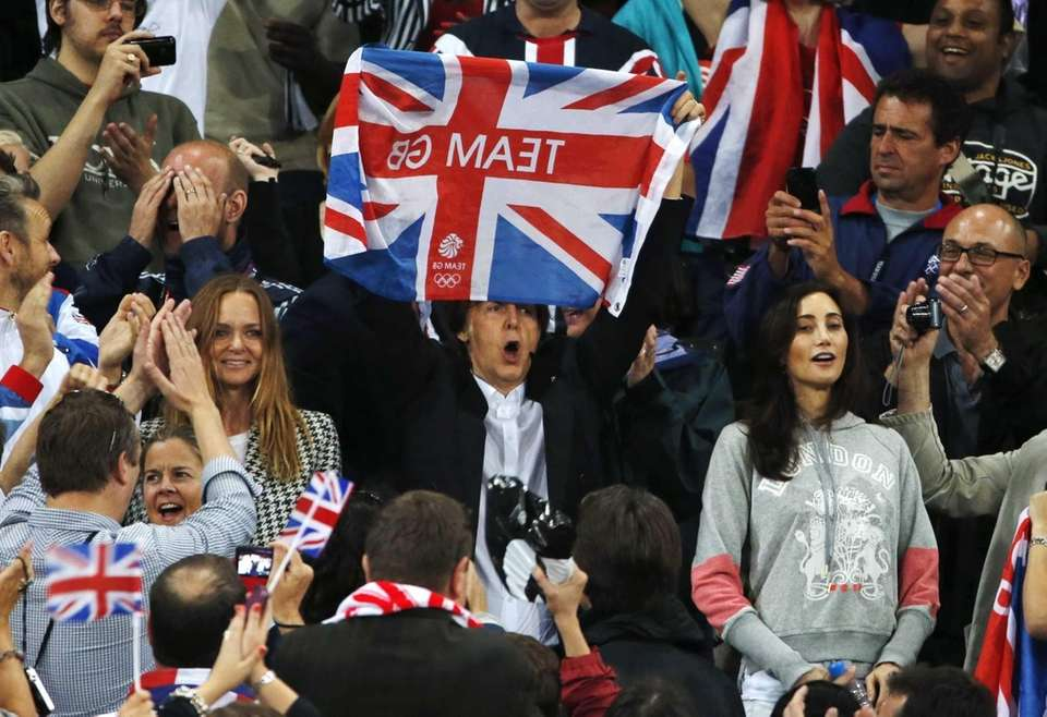 Performer Paul McCartney, center, celebrates Britain's gold medal