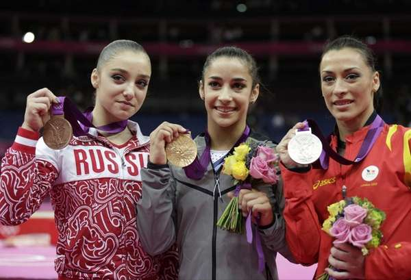 U.S. gold medallist gymnast Alexandra Raisman, center, Romania's