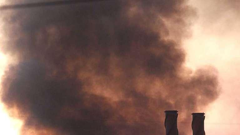 Fire crews pour water on a fire at