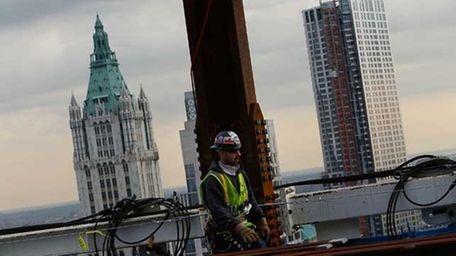 A construction worker walks near the eastern face
