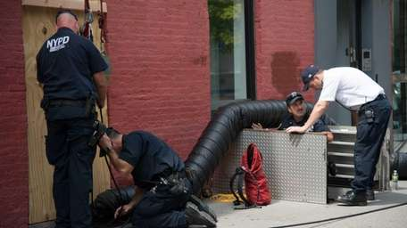 Members of the NYPD search for evidence in