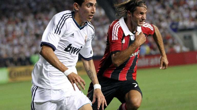 Real Madrid's Angel Di Maria beats AC Milan's