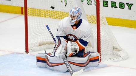 The puck flies past Islanders goaltender Thomas Greiss