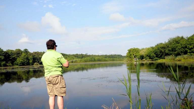 A fisherman casts into Lily Lake on Yaphank