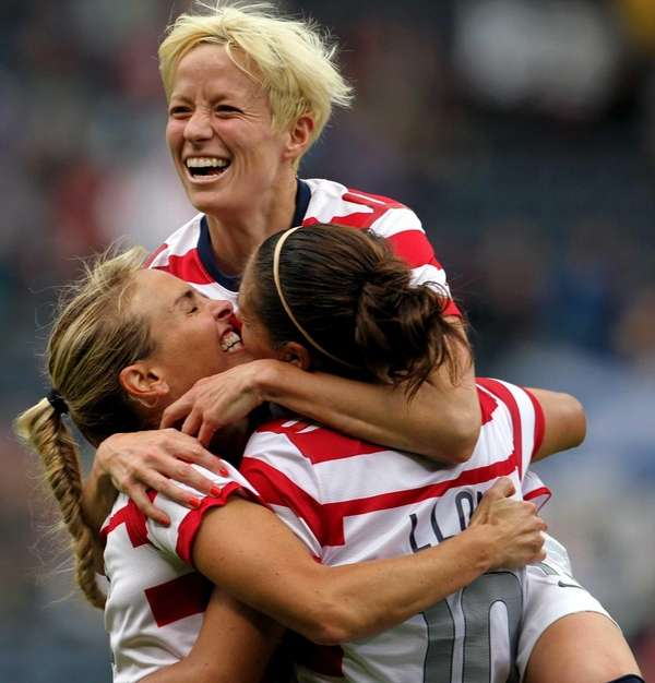 United States' Carli Lloyd, right, celebrates her third