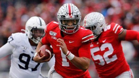 Ohio State quarterback Justin Fields, center, runs for