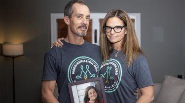 Steve Schmidt and Donna DeSousa-Schmidt, of Greenlawn, hold