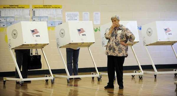 A voting inspector stands by while voters cast