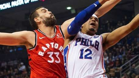 The 76ers' Tobias Harris, right, shoots as the
