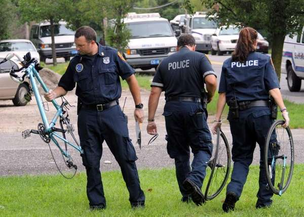Police remove pieces of a bicycle near Patchogue